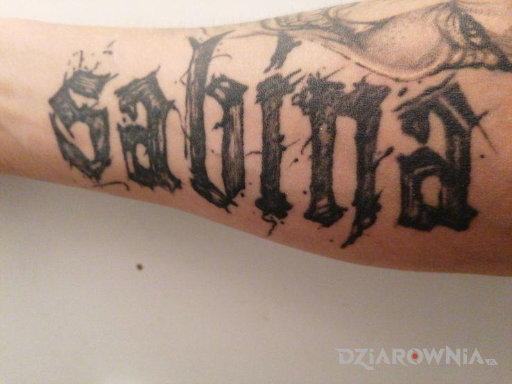 Tatuaż żeby nie zapomnieć jak ma żona na imię w motywie czarno-szare i stylu kaligrafia na przedramieniu