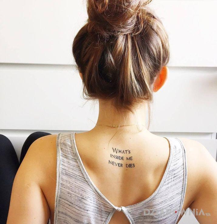Tatuaż co jest we mnie w motywie napisy i stylu kaligrafia na plecach
