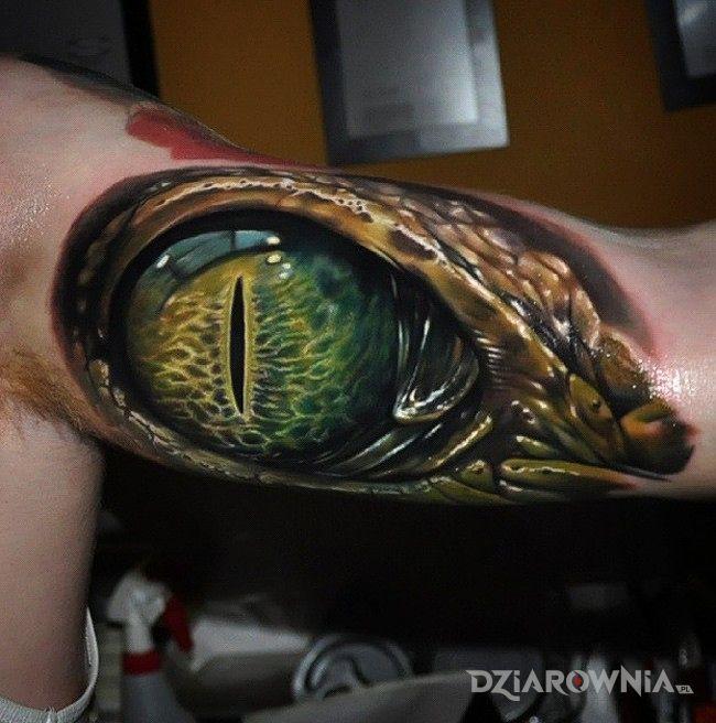 Tatuaż oko krokodyla w stylu realistyczne na ramieniu