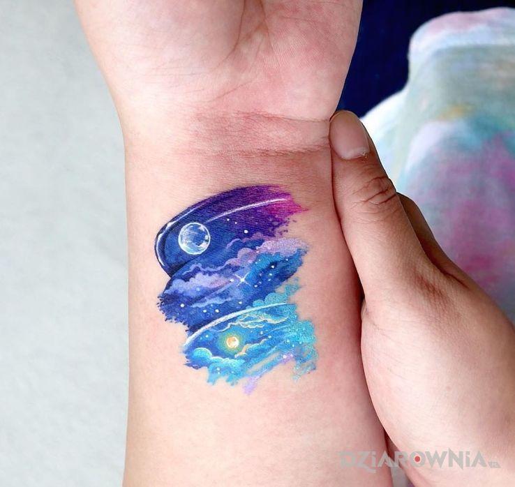 Tatuaż niebo w motywie kosmos i stylu watercolor na nadgarstku