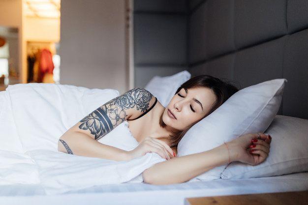 dziewcyzna z tatuażem w łóżku
