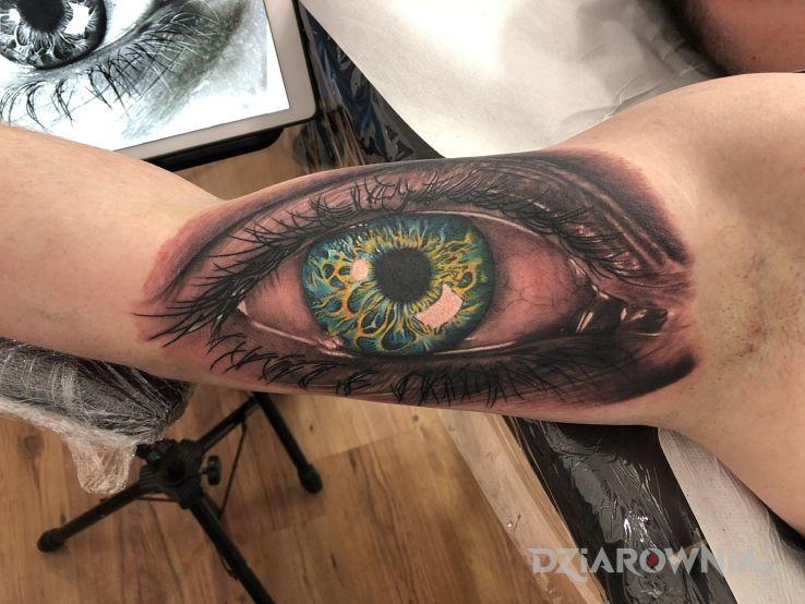Tatuaż oko na bicepsie w motywie 3D i stylu realistyczne na ramieniu