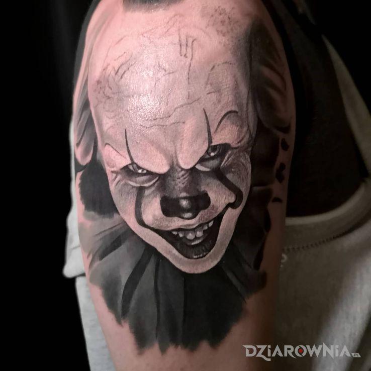 Tatuaż pennywise w motywie mroczne i stylu realistyczne na ramieniu