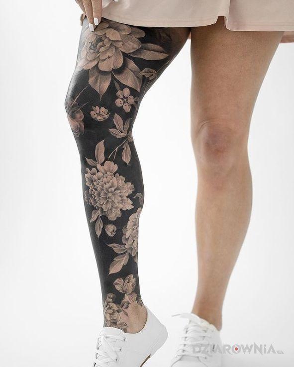 Tatuaż kwiaty na czarnym tle w motywie nogawki i stylu blackwork / blackout przy kostce