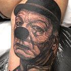 Tatuaż smutny klaun na bicepsie, motyw: twarze, styl: realistyczne