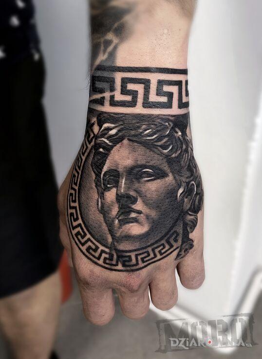 Tatuaż apollo w motywie twarze i stylu geometryczne na dłoni