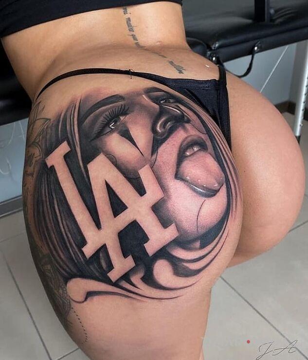Tatuaż laska z la w motywie twarze i stylu chicano na pośladkach