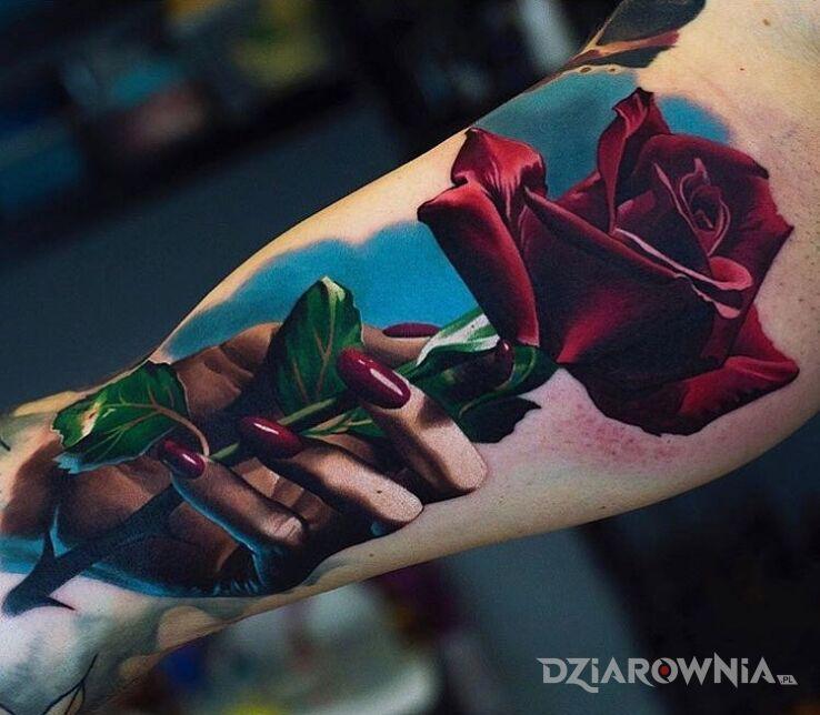 Tatuaż czerwona róża w dłoni w motywie kolorowe i stylu realistyczne na bicepsie