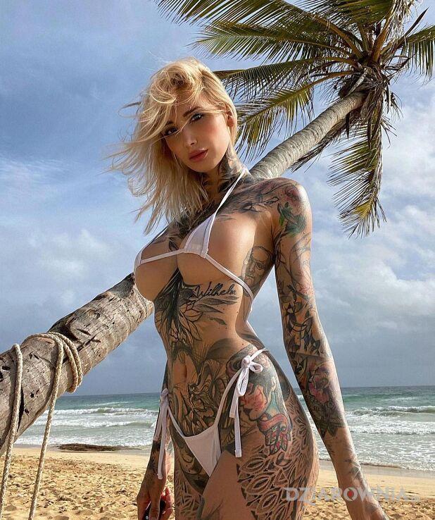 Tatuaż roztrzepane włosy pod palmą w motywie kolorowe i stylu graficzne / ilustracyjne na przedramieniu