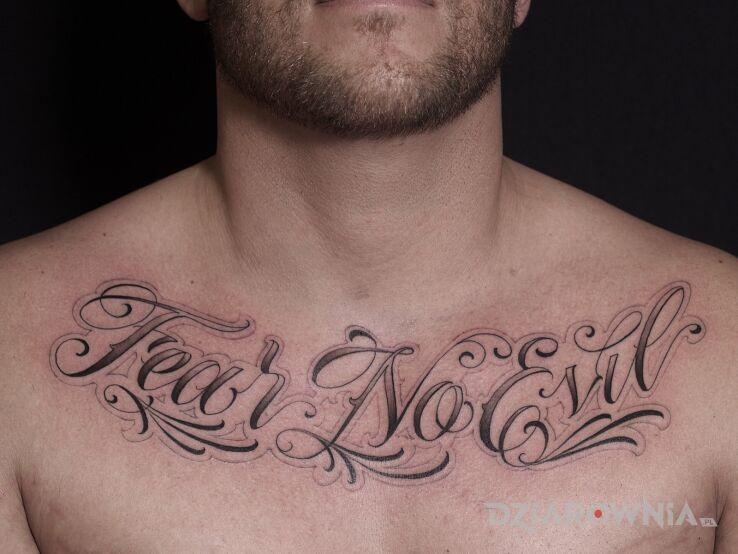 Tatuaż nie boj sie diabla w motywie czarno-szare i stylu kaligrafia na obojczyku