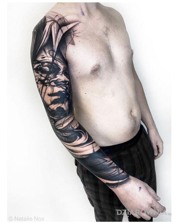 Tatuaż pomazana twarz w motywie czarno-szare i stylu blackwork / blackout na ręce