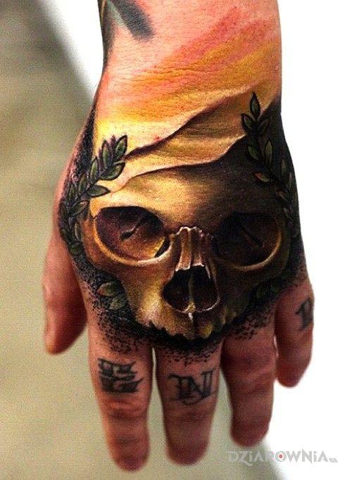 Tatuaż złota czacha w motywie czaszki na dłoni