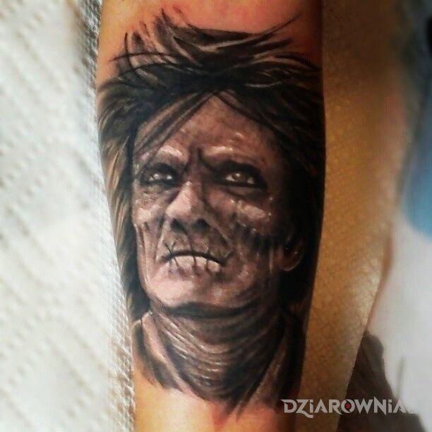Tatuaż jakiś stwór w motywie twarze na przedramieniu