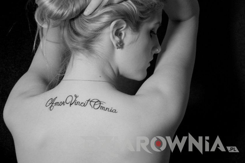 Tatuaż napis po łacińsku na plecach u dziewczyny