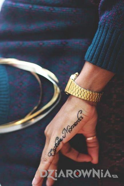 Krótki wytatuowany napis na boku dłoni kobiety
