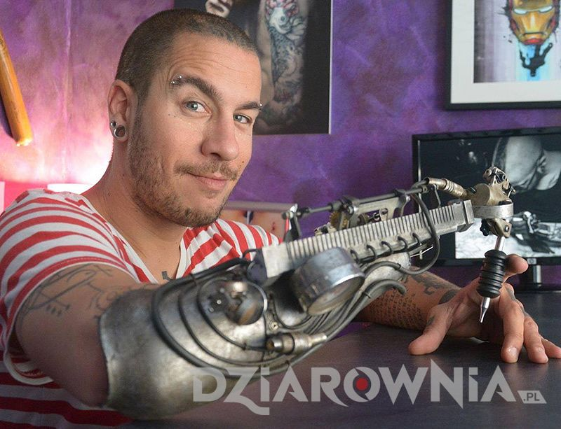 Tatuażysta bez ręki, który ma maszynkę do tatuowania w protezie